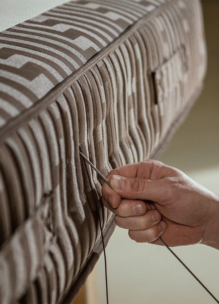 Kamjo employee sticks needle with thread into mattress